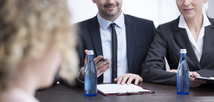 Body shot of two recruiters in suits conducting interview, candidate in foreground and out of focus
